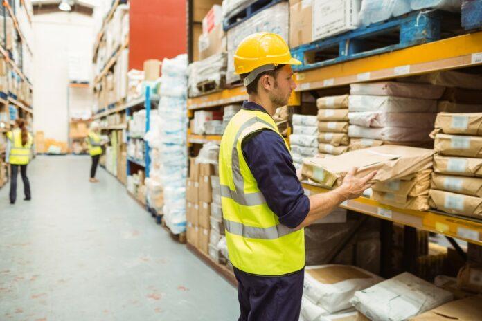Warehouse worker taking package in the shelf